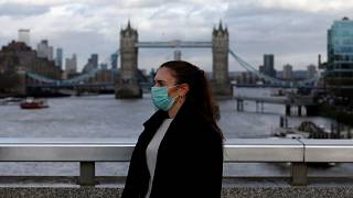 Image: A woman wearing a protective face mask on London Bridge in London