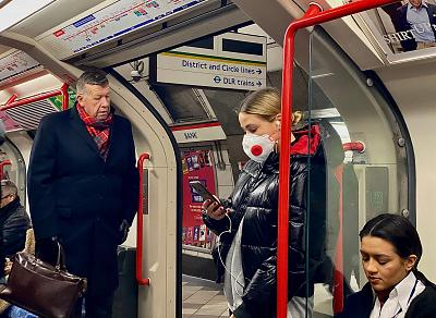 A woman wears a protective face mask as she travels on a London tube train on Tuesday.