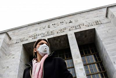 A woman wearing a respiratory mask exits from the Palace of Justice in Milan, on Thursday.