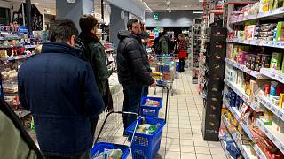 Image: Customers wait in line to pay at a supermarket in Milan on March 7,