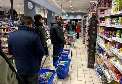 Customers wait in line to pay at a supermarket in Milan.
