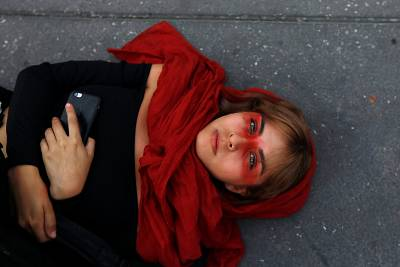 A woman lies on the floor during a protest to mark International Women\'s Day at Zocalo Square in Mexico City, Mexico, on Sunday.