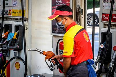An employee wearing a face mask fills up a car at a gas station in Bangkok on Monday.