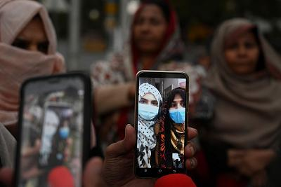 Parents and relatives of Pakistani students in the Chinese city of Wuhan, where the outbreak of the COVID-19 coronavirus began, hold mobile phones during a video call with them during a protest Feb. 19, 2020, to demand that Pakistan\'s government evacuate their loved ones in Islamabad.