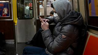 Image: A man wearing a face mask reads his phone on the subway in New York