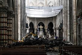 Rubble and the cross at the altar inside the the Notre Dame de Paris Cathedral after it sustained major fire damage the previous month. 15 May 2019