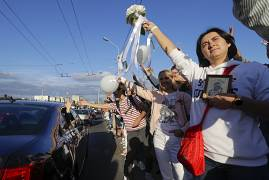 People greet each other waving flowers and white balloons as they gather in a street to demand fair presidential elections. In Minsk, Belarus. August 13, 2020