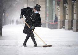 Ein Angestellter des Hotels Adlon fegt den Schnee vom Gehweg am Pariser Platz in Berlin, Deutschland, 08.02.2021