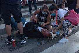 People try to help an injured man during a protest in Belgrade, Serbia. July 8, 2020