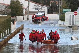 Firefighters wading in a flooded street of La Faute-sur-Mer as a result of a storm on March 1st, 2010.