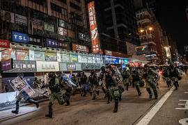 Riot police charge protesters on Nathan Road, Hong Kong, on 1 December 2019