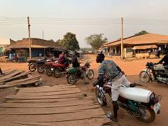 Young men wait for customers on their motorbike taxis, called 'boda-bodas'