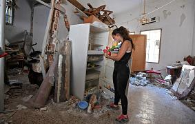 A woman clears rubble in her damaged house in Beirut on August 6, 2020, after a massive explosion shook the Lebanese capital