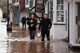 A woman carries a dog as she wades through flood water on Teme Street in Tenbury Wells, after the River Teme burst its banks in western England. 16 February, 2020.