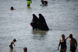Two women leave the sea after bathing at 'Pointe Rouge' beach in Marseille, France. July 27, 2020