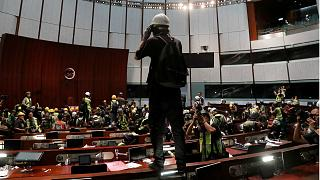 Protesters stand on the tables of the parliament chamber
