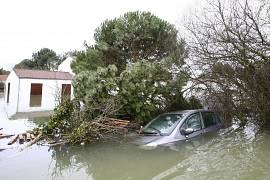 Flooded houses and a car are seen in La Faute sur Mer.