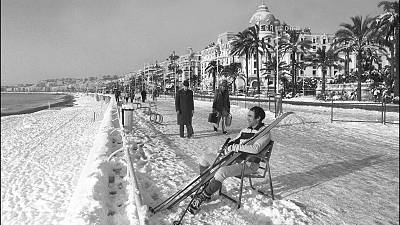 A man takes off his skis to rest at the Promenade des Anglais after  rare heavy snowfall in Nice, France. January 8, 1985