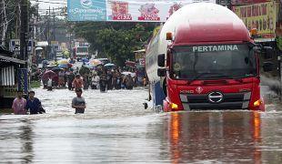 Un camion se fraie un chemin à travers les rues inondées de Jatibening près de Jakarta en Indonésie