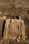 Tombes à crémation en cours de fouille et enclos funéraire avec petit monument, installés le long d'un chemin de desserte