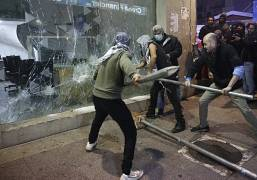Anti-government protesters smash a bank widow, during ongoing protests against the Lebanese central bank's governor and against the deepening financial crisis. 14 Jan. 2020.