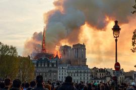 People looking at smoke and flames rising during a fire at the landmark Notre-Dame Cathedral in central Paris on April 15, 2019