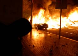 Una persona observa un coche en llamas en Barcelona, el 16 de octubre de 2019.