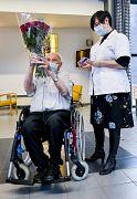 Il belga Jos Hermans, 96 anni, al centro, tiene in mano un mazzo di fiori dopo aver ricevuto il vaccino COVID-19 presso la casa di cura Sint Pieter a Puurs, in Belgio, lunedì