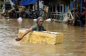 Un homme se déplace dans une boîte en polystyrène dans une rue inondée de Jakarta en Indonésie, le 2 janvier