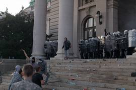 Protesters charge the steps of the Serbian parliament as riot police stand guard during a protest in Belgrade, Serbia. July 8, 2020