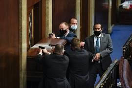 U.S. Capitol Police with guns drawn stand near a barricaded door as protesters try to break into the House Chamber at the U.S. Capitol, Washington, USA. January 6, 2021