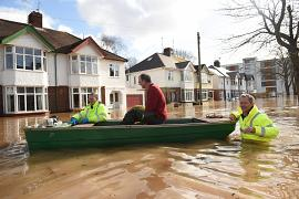 A resident is rescued from a home in a boat by the emergency services amid flooding in Hereford, western England.