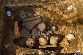 Tombe à crémation constituée d'un amas d'ossements humains brûlés surmonté de cruches en céramique et d'un petit balsamaire en verre.