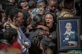 Relatives hold photographs of the victims at a mass funeral at the Holy Trinity Cathedral in Addis Ababa, Ethiopia