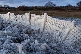 Ein mit Eis bedeckter Zaun steht am Ufer der Kieler Förde in Strande, Deutschland. Freitag, 12.02.2021
