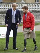 Britain's Prince Harry walks with Rugby League World Cup 2021 ambassador James Simpson in the gardens at Buckingham Palace in London. 16 January 2020.