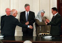 يبدو الرئيس كلينتون وكأن الرئيس المصري حسني مبارك يصافح زعيم منظمة التحرير الفلسطينية ياسر عرفات في الغرفة الشرقية للبيت الأبيض بعد توقيع اتفاق الشرق الأوسط. 1995