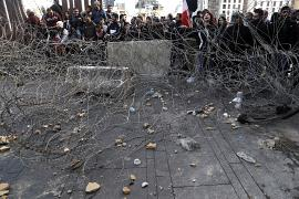 Anti-government protesters stand behind barbed wires that set by security force in downtown Beirut, Lebanon. 27January 2020.