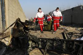 The rescue workers carry the body of a victim of a Ukrainian plane crash among the debris of the plane in Shahedshahr southwest of the capital Tehran, Iran. 8 January 2020.