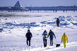 Menschen spazieren auf dem schneebedeckten Strand in Bansin, Usedom, 12.02.2021