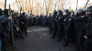 Police officers face far-right movements activist protesting against land sale reform in front of Parliament in Kiev on December 17, 2019.