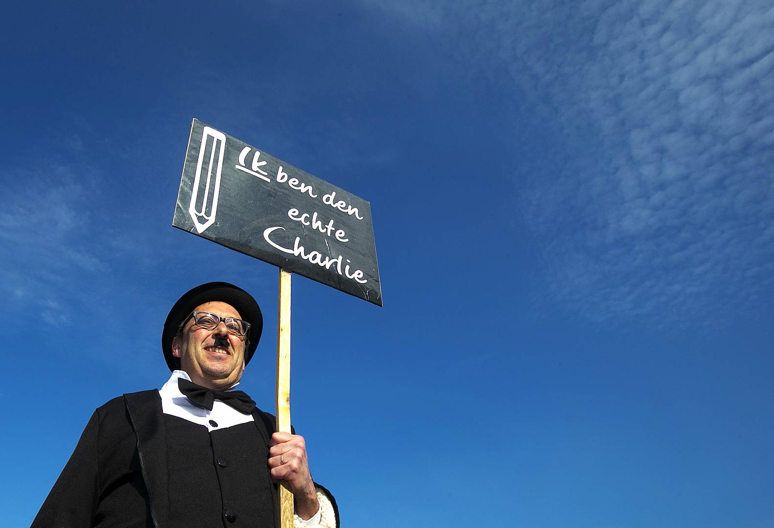 A reveller dressed as Charlie Chaplin displays a placard reading