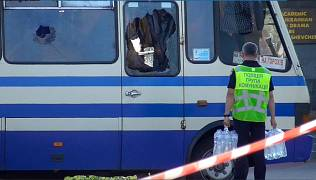 A policeman brings water for hostages held in a bus in the city centre of Lutsk, Ukraine. July 21, 2020