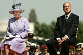 Britain's Queen Elizabeth (L) and French President Jacques Chirac (R) watch events at the Commonwealth War Graves Cemetery in Bayeux, northern France, June 6, 2004.