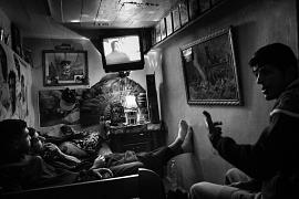Friends relax and watch television in their diki, a private space they have created in a converted storeroom, in Bab el-Oued, Algiers, Algeria, on 6 December 2016.