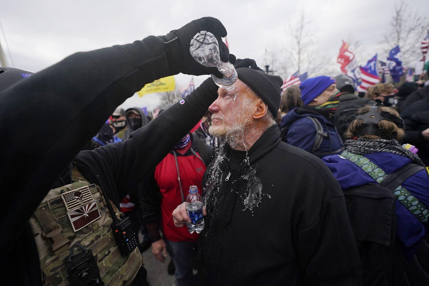 Seorang demonstran matanya dibilas dengan air setelah menghadapi polisi di Capitol di Washington, AS. 6 Januari 2021