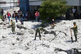 Soldiers try to clear away ice as residents look on after a heavy storm of rain and hail which affected some areas of the city in Guadalajara