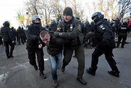 Police officers detain an activist during clashes during a protest against land sale reform in front of the Ukrainian Parliament in Kiev on December 17, 2019.