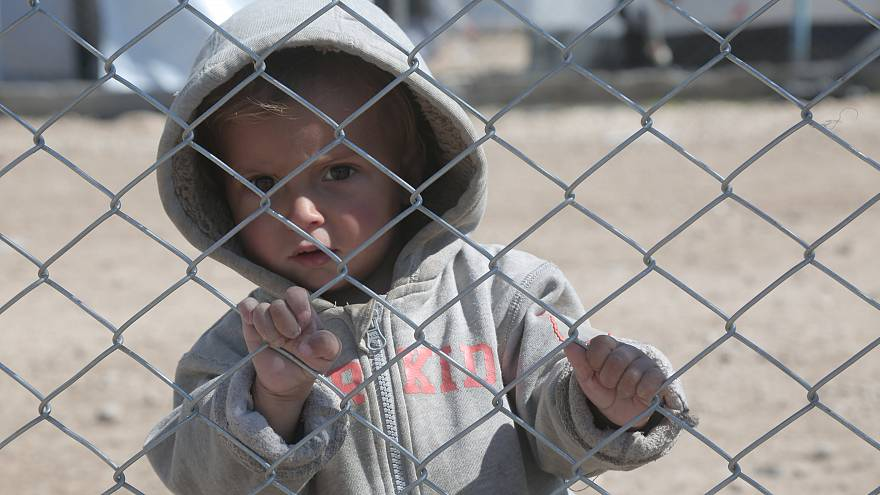 A child looks through a chain linked fence at al-Hol displacement camp