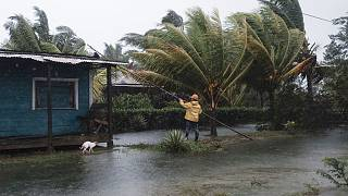 A man fixes the roof of a home surrounded by floodwaters brought on by Hurricane Eta in Wawa, Nicaragua.
